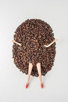 Die beine und arme einer mädchenpuppe ragen aus dem stapel kaffeebohnen heraus.