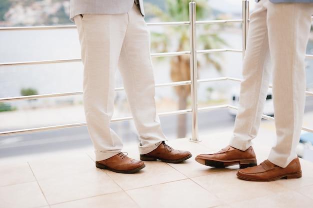 Die beine von zwei männern, die auf dem balkon stehen, schließen den bräutigam und seinen trauzeugen während der