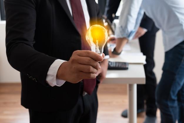 Die beleuchtete glühbirne in der hand eines geschäftsmanns vergleicht seine neue idee