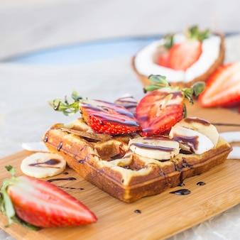 Die belgische waffel mit obst- und schokoladensauce wird auf einem holzbrett serviert