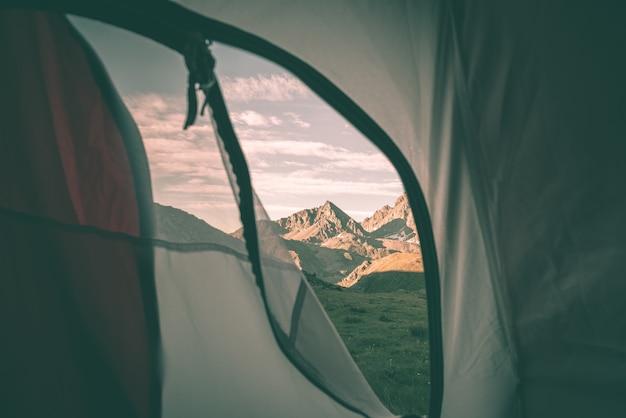 Die berglandschaft sonnenaufgang vom innenraum des campingzeltes heraus betrachten.