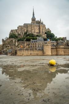 Die berühmte abtei mont saint-michel spiegelt sich bei ebbe am strand und eine bowlingbahn für boote, normandie, frankreich