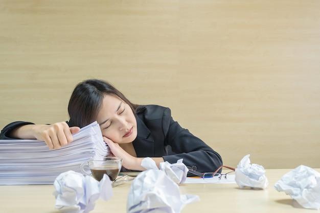 Die berufstätige frau der nahaufnahme, die nachdem sie müde von ihrer arbeit schläft