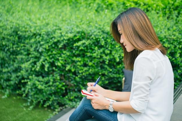 Die berufstätigen frauen, die am park, arbeitende frauenarbeitsgeschäfts-jobverfasser im freien schreiben, schreiben text in notizbuch