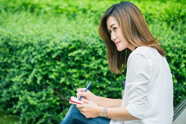 Die berufstätigen frauen, die am park schreiben, arbeitende frauen im freien bearbeiten geschäftsjob
