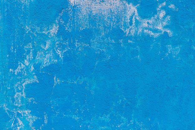 Die beschaffenheit der betonzementwand, die in der blauen farbe mit weiß gemalt wird, spritzt. hintergrund für tapeten