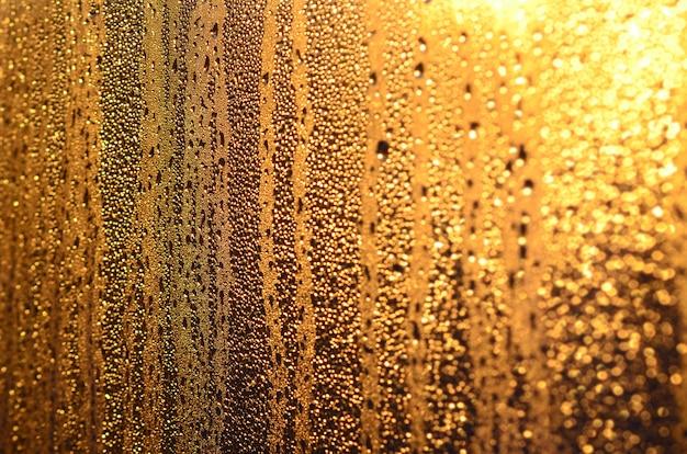 Die beschaffenheit des beschlagenen glases mit vielen tropfen und tropfen der kondensation gegen das sonnenlicht im morgengrauen
