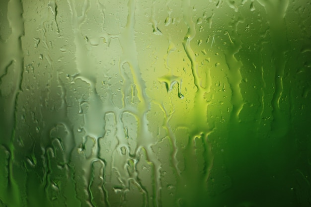 Die beschaffenheit des regens fällt auf das fensterglas auf grünem hintergrund