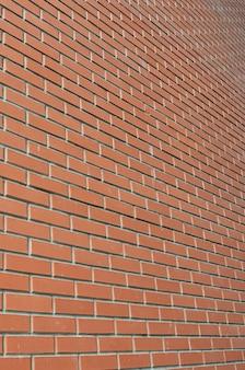 Die beschaffenheit einer hohen backsteinmauer von vielen reihen roten ziegelsteinen, die in perspektive ausdehnen
