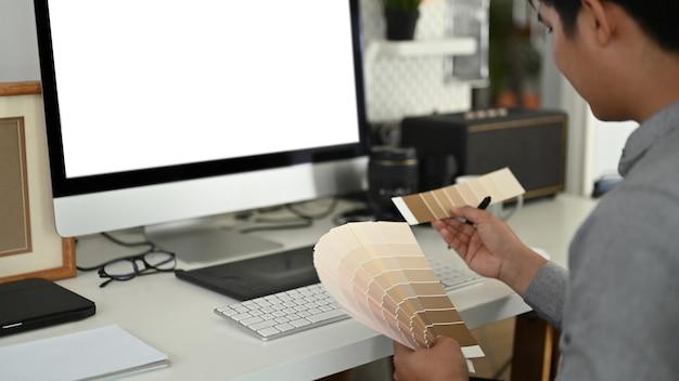 Die beschnittene aufnahme eines grafikdesigners oder fotografen wählt farbmuster für ein designprojekt in seinem büro aus.