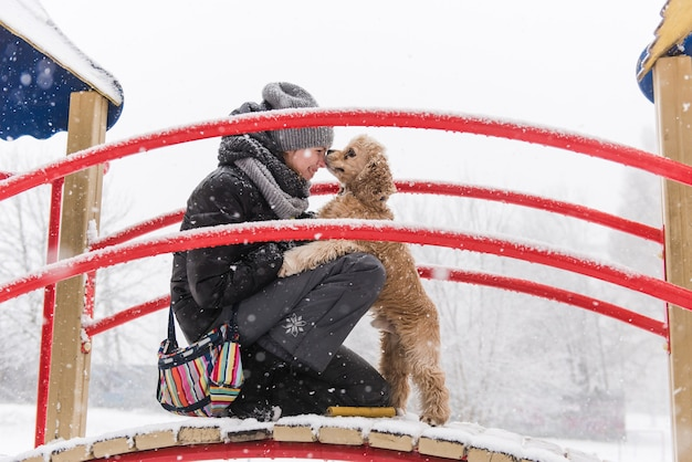 Die besitzerin und ihr hund küssen die nase während des winterspaziergangs