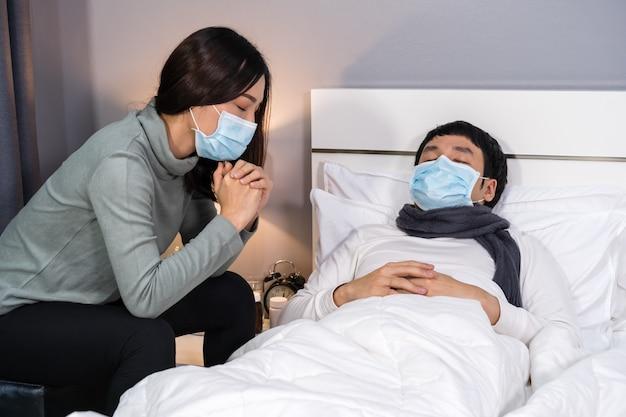 Die besorgte frau kümmert sich um ihren kranken ehemann, während er zu hause im bett schläft. die menschen müssen eine medizinische maske tragen, die vor einer coronavirus-pandemie schützt