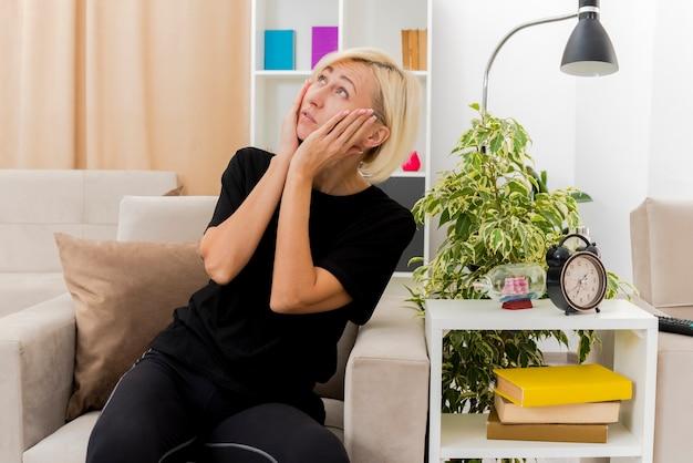Die besorgte schöne blonde russische frau sitzt auf dem sessel und legt die hände auf das gesicht, das nach oben schaut