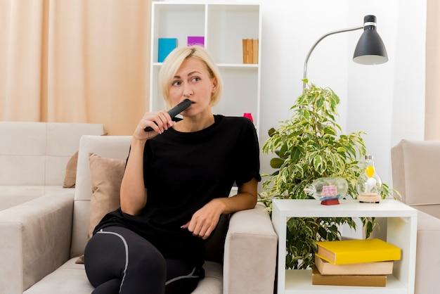 Die besorgte schöne blonde russische frau sitzt auf dem sessel und setzt die fernbedienung des fernsehers auf den mund, der die seite innerhalb des wohnzimmers betrachtet