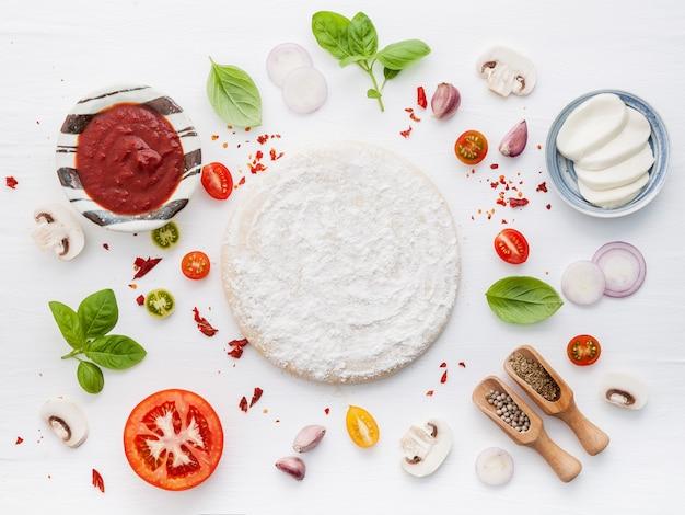 Die bestandteile für selbst gemachte pizza auf weißem hölzernem hintergrund.