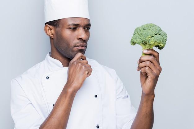 Die beste zutat für sein essen auswählen. nachdenklicher junger afrikanischer koch in weißer uniform