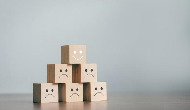 Die besten business services bewerten das kundenerlebnis. sortiert nach service-level zufriedenheits-umfragekonzept wählen sie bei einem business-holzklotz ein smiley-gesicht auf dem obersten holzklotz.