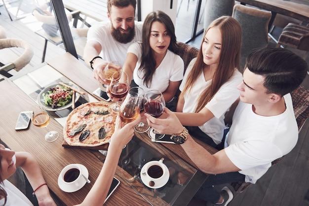 Die besten freunde versammelten sich am tisch mit leckerem essen und gläsern rotwein, um einen besonderen anlass zu feiern.