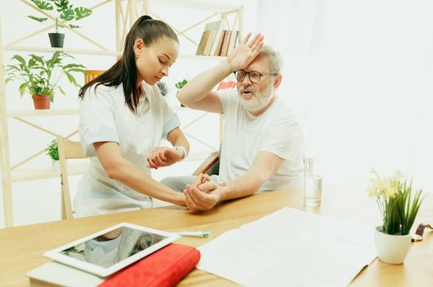 Die besuchende krankenschwester oder der gesundheitsbesucher, der sich um den älteren mann kümmert