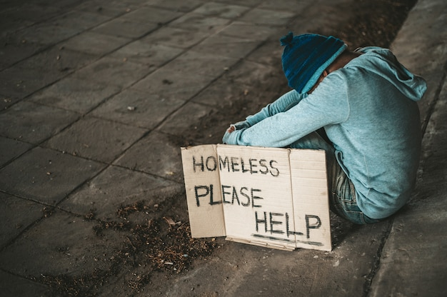 Die bettler sitzen mit einer obdachlosen nachricht unter der brücke. bitte helfen sie.