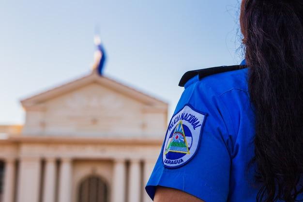 Die bewaffnete sandinistin der polizei schützt den nationalen managua-palast in nicaragua vor fsln-protesten