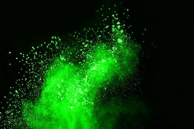 Die bewegung der abstrakten staubexplosion eingefrorenes grün auf schwarzem hintergrund.