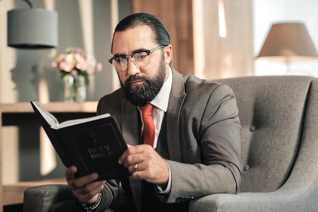 Die bibel lesen. dunkelhaariger bärtiger reifer mann, der seine zeit beim lesen der bibel genießt