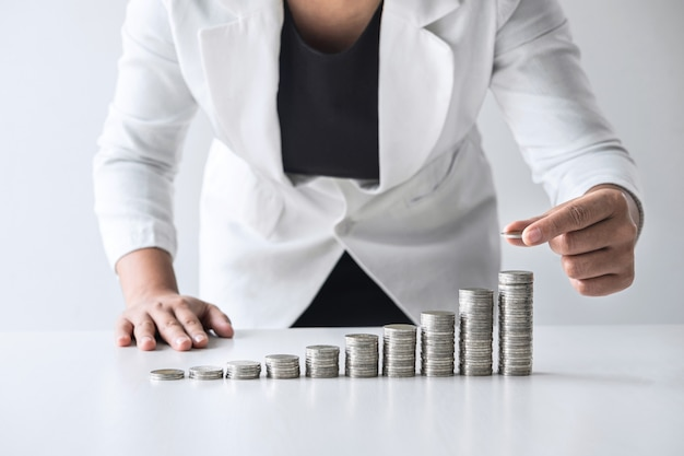 Die bilder des wachstums münzen stapelnd und die geschäftsfrau übergeben das setzen der münze für die planung des wachsenden geschäftsgewinns steigern und die einsparungen und sparen geld für zukünftigen plan und pensionskassenkonzept