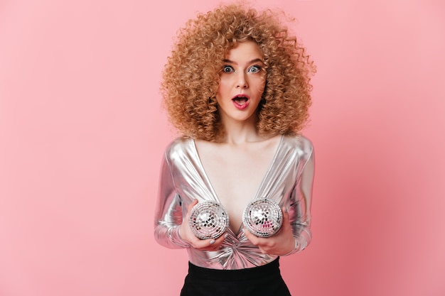 Die blauäugige dame in strahlendem oberteil starrt erstaunt in die kamera und hält discokugeln in der nähe ihrer brüste.