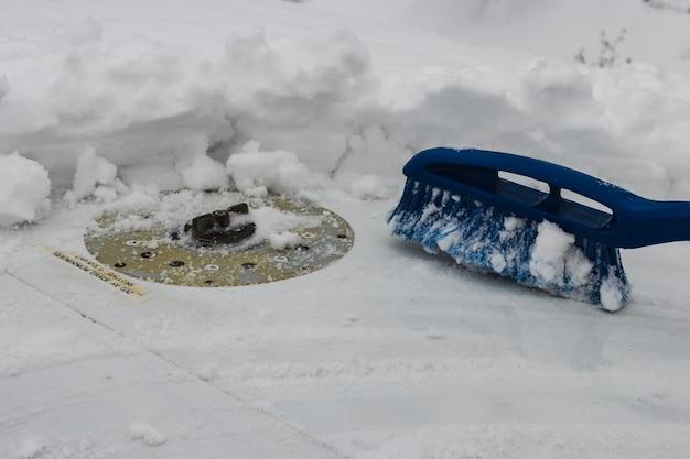 Die blaue entfernungsbürste entfernt schnee vom flugzeugflügel