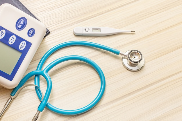 Die blauen stethoskope auf hölzerner tabelle