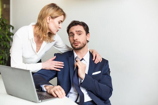 Die blonde chef-geschäftsfrau verführt ihren männlichen assistenten, der mit einem laptop arbeitet