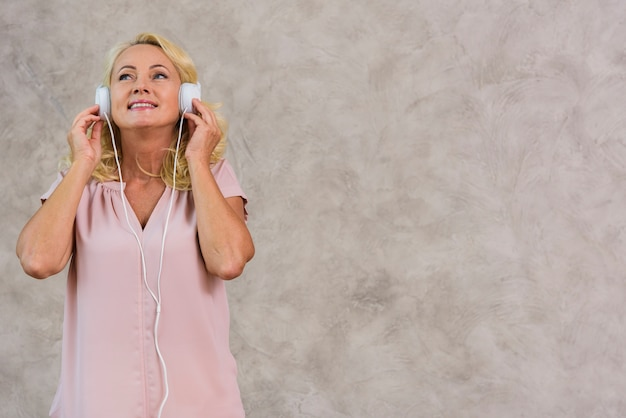 Die blonde dame, die musik auf kopfhörer hört, stellte mit kopienraum ein