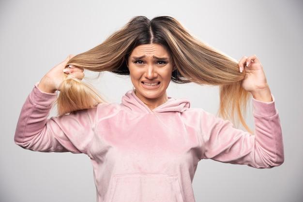 Die blonde dame im rosa sweatshirt ist unzufrieden mit ihrem trockenen haar oder ihrer haarfarbe.