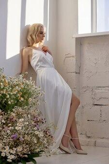 Die blonde frau im weißen hochzeitskleid steht in der nähe des fensters vor einem strauß wilder blumen