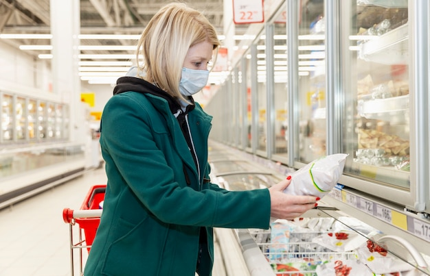 Die blonde frau in einer medizinischen maske kauft im supermarkt ein. selbstisolation bei einer pandemie.