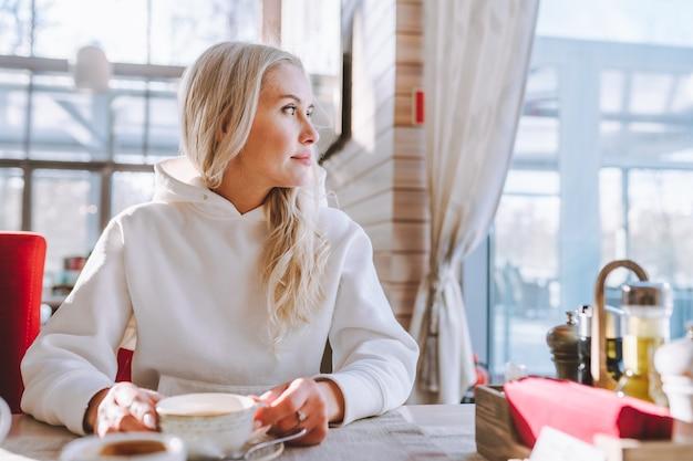 Die blonde frau mittleren alters sitzt allein im café mit einer tasse kaffee und schaut zum fenster.