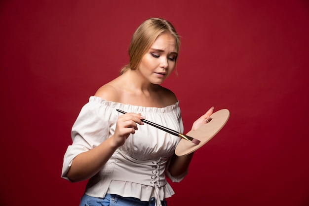 Die blonde künstlerin hält eine palette und pinsel und sieht konzentriert und konzentriert auf ihren job aus.