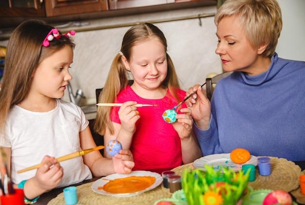 Die blonde mutter zeigt ihren töchtern, wie man ostereier zu hause in der küche dekoriert.