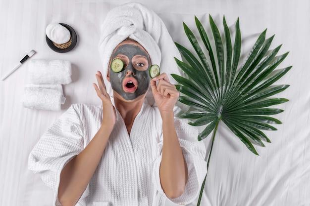 Die blondine posiert in einem weißen kittel und ein handtuch auf dem kopf posiert mit einer tonmaske