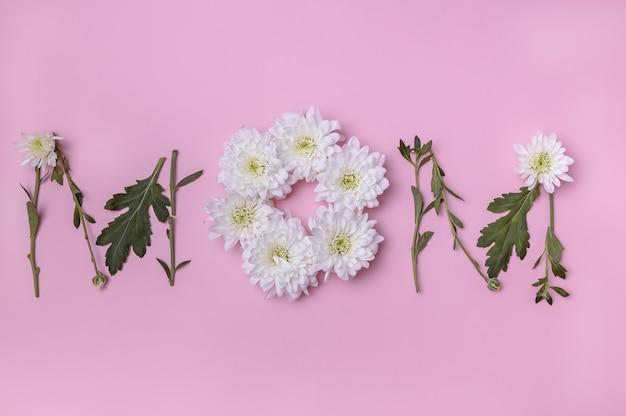 Die blüten der weißen chrysanthemen sind in form der wortmama ausgelegt