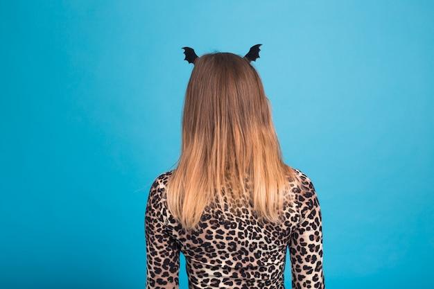 Die böse frau mit einem hüftschläger auf dem kopf. kostüm für halloween auf blauer wand, rückansicht