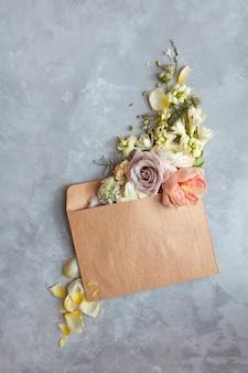 Die botschaft im brief. schöner blumenstrauß in einem umschlag auf steingrauem hintergrund als konzept für den urlaub, flach.