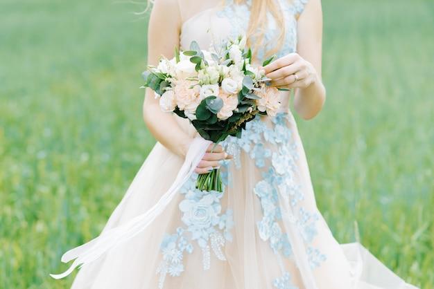 Die braut berührte mit ihrer hand ein zartes und schönes bouquet