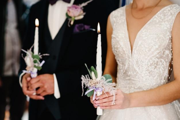 Die braut, bräutigam hält in händen hochzeitskerze. spirituelles paar, das kerzen während der hochzeitszeremonie hält.