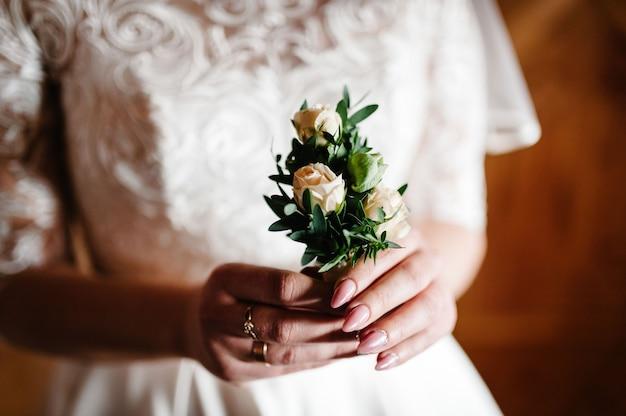 Die braut, die in der hand nahaufnahme der knopflochblumen des bräutigams mit weißen rosen hält