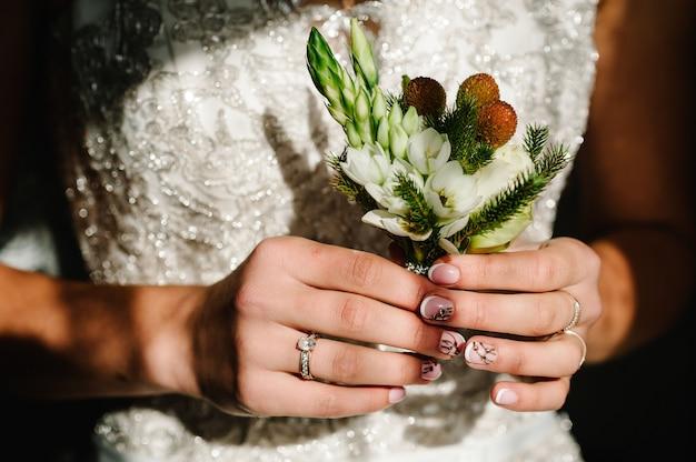 Die braut, die in der hand nahaufnahme des knopflochs des bräutigams weiße blumen und grün und grün hält. vorbereitungen der braut. hochzeit morgen konzept.