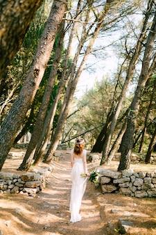 Die braut geht den weg zwischen den bäumen im hain entlang und hält einen blumenstrauß in der rückansicht