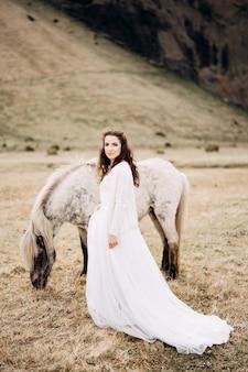 Die braut geht neben einem weißen pferd über das feld