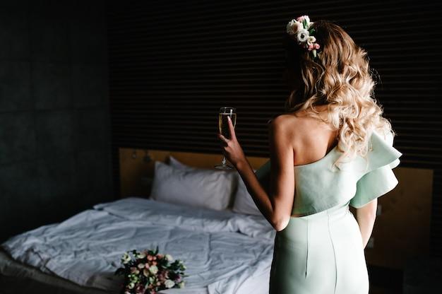 Die braut hält ein glas champagner in der hand und tritt in der nähe des bettes im zimmer zurück